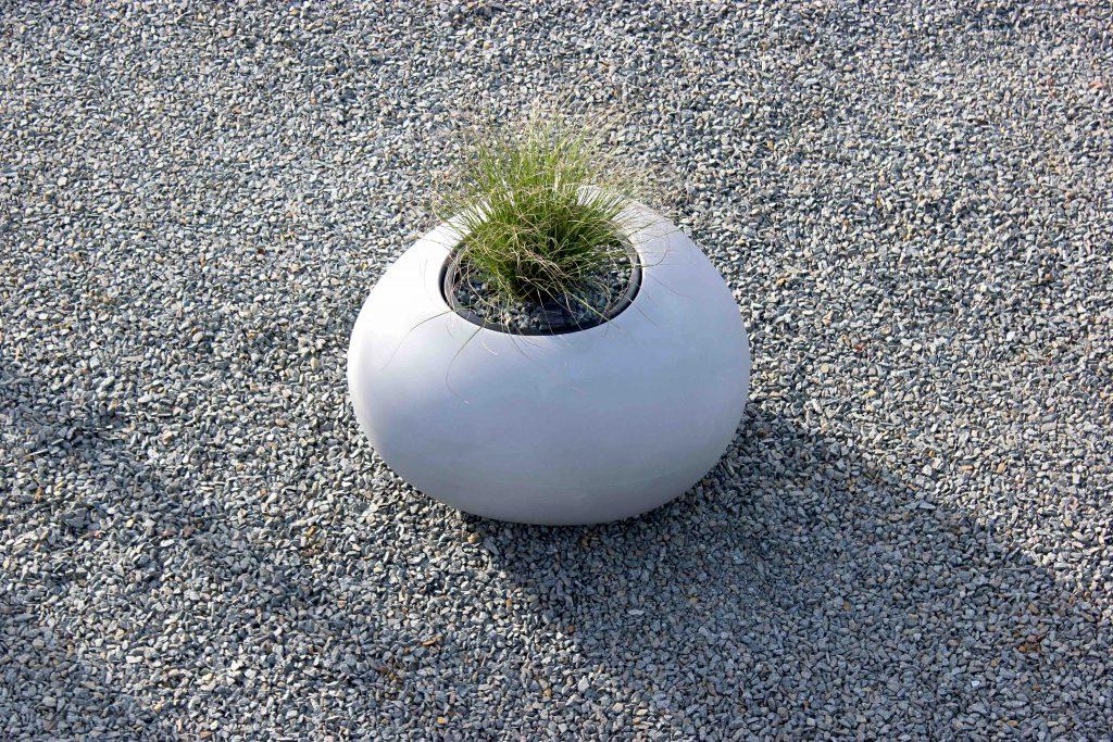 Voortuin en oprit met grind, bloembak doorbreekt de eentonigheid en bakent zones om te parkeren af