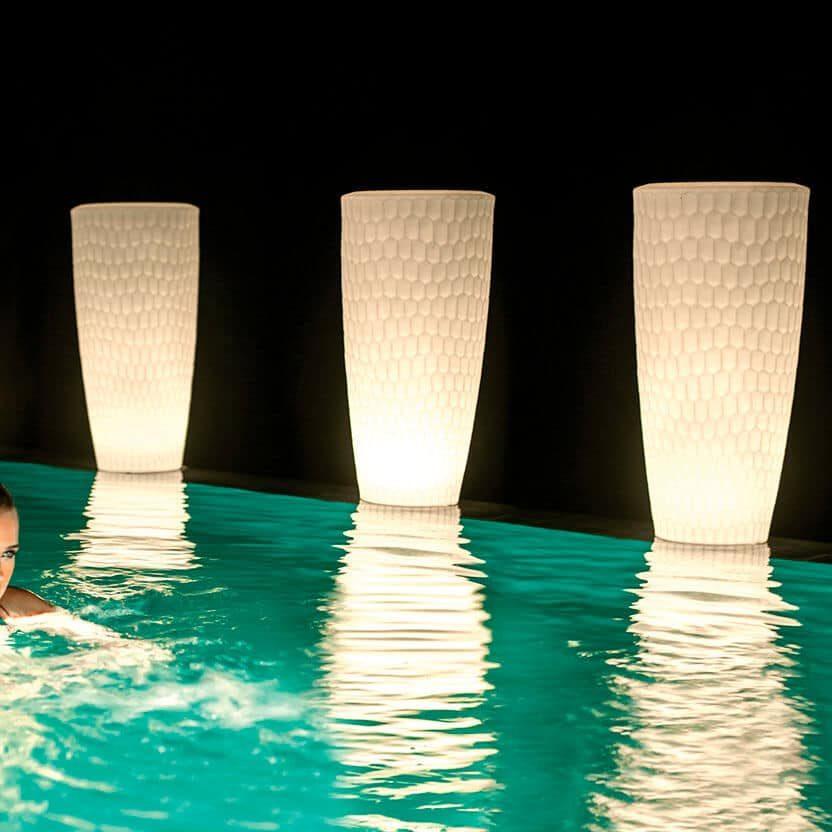 Drie bloempotten met geïntegreerde sfeerverlichting aan de rand van het zwembad